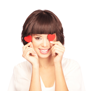 Portrait of a smiling young woman covering her one eye with a heart
